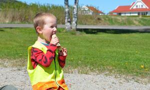 Bildet viser en gutt spise pølser på Nøklebytangen!