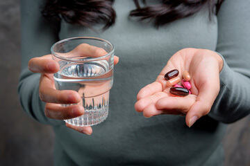 bs-Woman-Holding-Pill-412356103-360
