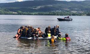 Bildet viser elever fra Bergerbakken skole som har fylt opp en liten jolle med mange personer. Den synker.