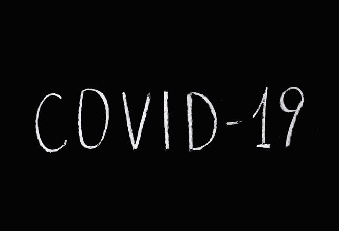 Bildet viser noen som har skrevet Covid-19 på en tavle.