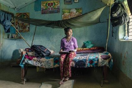 Bildet viser ei jente som sitter på en seng med en bok i hendene.