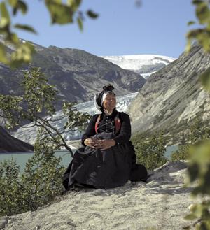 <br><i>Eit praktfullt panorama inn mot Nigardsbreen, ein arm av Jostedalsbreen. Drakta er i alle delar kopi av gamle plagg frå området rundt Jostedal. Dei gamle plagga er i samlinga til Breheimsenteret i Jostedal</i>